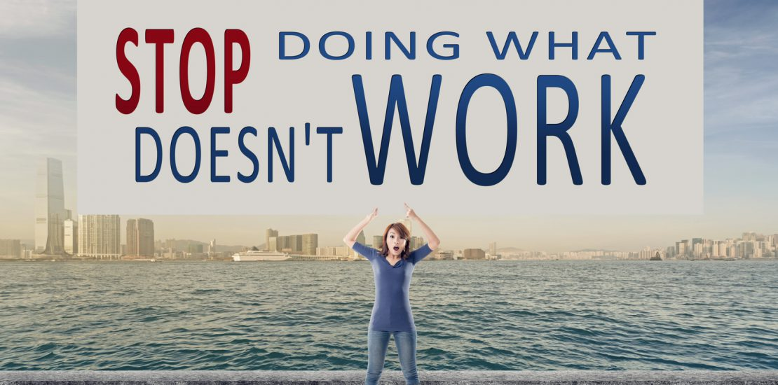 Stop doing what doesn't work, words on blank board hold by a young girl in the outdoor.